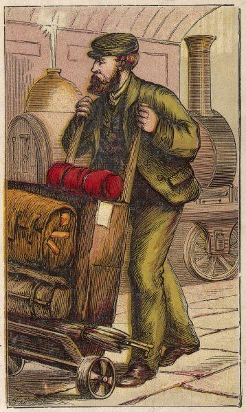 A station porter carries a passenger's baggage on his trolley