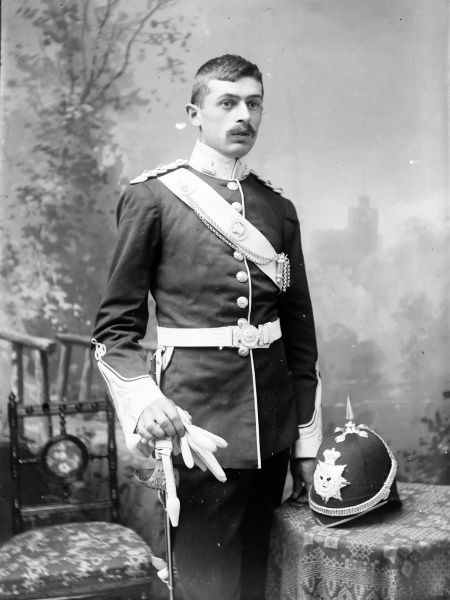Portrait of a young army officer belonging to the Brecknockshire Battalion. He is in full dress uniform, complete with sword, helmet and white gloves, in the photographer's studio
