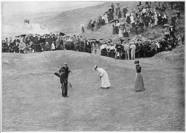 A lady putts out during a match at Royal Portrush in Northern Ireland, whilst a crowd of spectators looks
