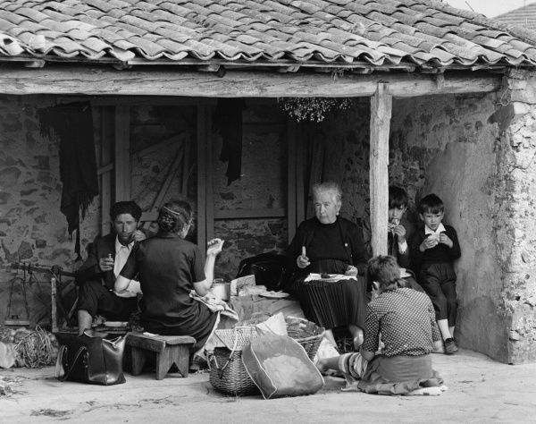 A Portuguese family having a picnic in the shade of a low roof