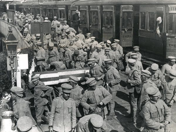 Portuguese soldiers disembarking from an English train, First World War. They are probably arriving in Hampshire, to work in the New Forest to help produce timber for the war effort. Date: 1917-1918