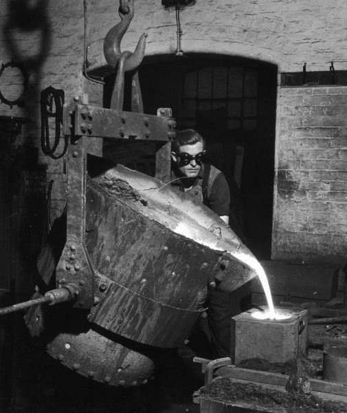 A metalworker wearing protective eye goggles pours molten metal in to a mould from a huge crucible container, attached to an immense hook, into a small mould. Photograph by Heinz Zinram