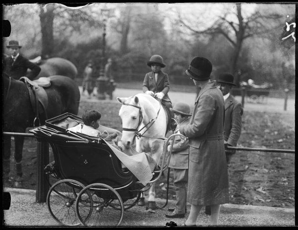 A fashionable young mother, (or nanny) pushing her baby in a splendid pram, stops to pass the time of day with some horse riders on Rotten Row, Hyde Park, central London