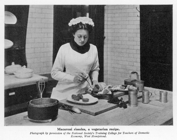 A photograph from the National Society's Training College for Teachers of Domestic Economy showing a female student preparing vegetarian macaroni rissoles