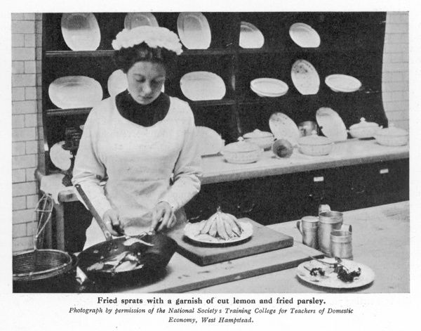 Photograph of a student at the National Society's Training College for Teachers of Domestic Economy, preparing a dish of fried sprats garnished with lemon & parsley