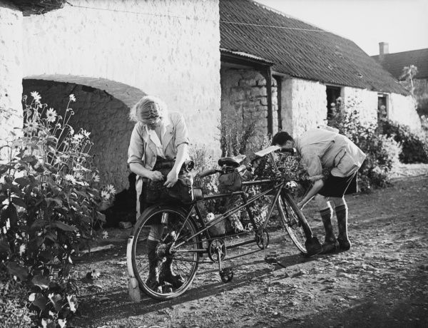 A young couple prepare their tandem bicycle for an early morning ride, the acme of seeing England at its very best