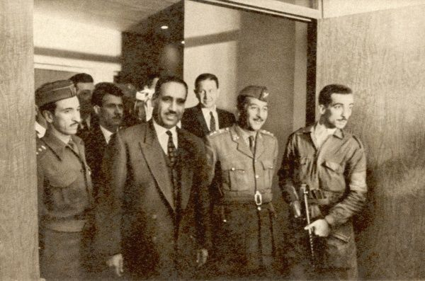 President Abdul Mohammed Arif (wearing suit) arrives for his first press conference after becoming president of Iraq, following a coup