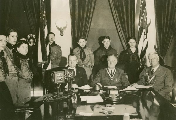 US President and Scouting officials sit at a table behind microphones while seven Boy Scouts stand behind them
