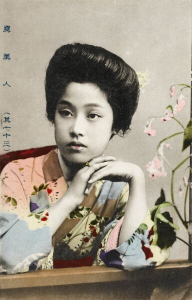A Pretty young Japanese girl in a floral kimono, posing seated at a table alongside some orchids