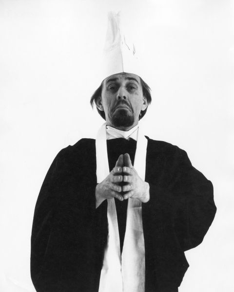 A priest (or chef?) with his hands together. Date: 1960s