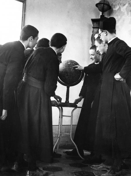 A group of young Italian priests studying a globe during a Geography lesson, Rome, Italy. Date: 1930s