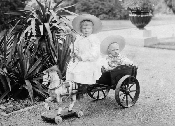Prince Edward and Albert of York (later King Edward VIII and King George VI respectively) shown riding a toy horse and cart in 1897