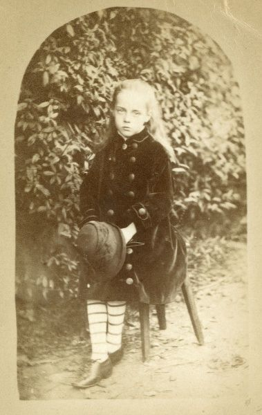 Princess Beatrice Mary Victoria Feodore, later Princess Henry of Battenberg (1857-1944), the fifth daughter and youngest child of Queen Victoria and Prince Albert. Seen here as a young girl, posing in a garden in a velvet coat and stripy stockings