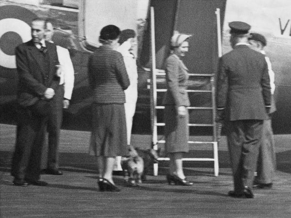 Princess Elizabeth (later Queen Elizabeth II) with others at an airport, standing near the steps to a plane. Two corgi dogs stand behind her