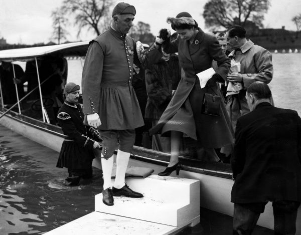 Princess Elizabeth is helped ashore from the launch 'Enchantress' by Bert Barry, former world professional sculling champion, dressed in his red doggetts coat and badge regalia. Date: 17th March 1951