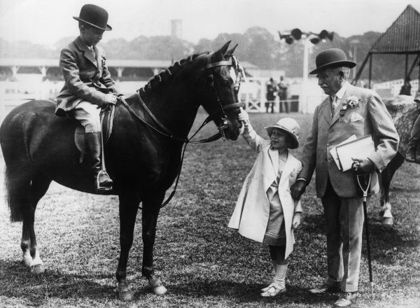 Princess Elizabeth of York (Queen Elizabeth II) pictured showing an early interest in horses at an unidentified event in the early 1930s. Date: c.1933