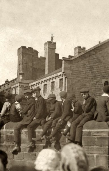 A prisoner can be seen on the roof of Armley Gaol in Leeds, West Yorkshire. The event has attracted spectators from the neighbourhood. Boys in caps sit on a wall beside the prison
