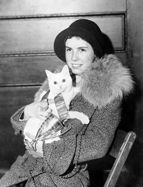 A proud lady owner shows off her cat, which won first prize in an American cat show. Date: 1931