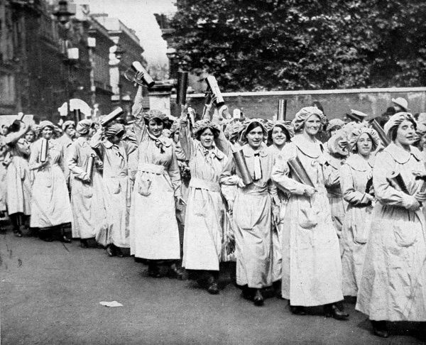 Female workers from a munitions factory are shown taking part in a procession celebrating the role of women during the First World War. They are seen waving polished shell-cases