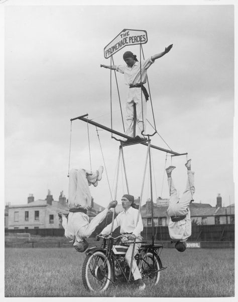A motorcycle acrobat troupe called 'The Promenade Percies' practise their act involving balance on a trapeze attached to the bike