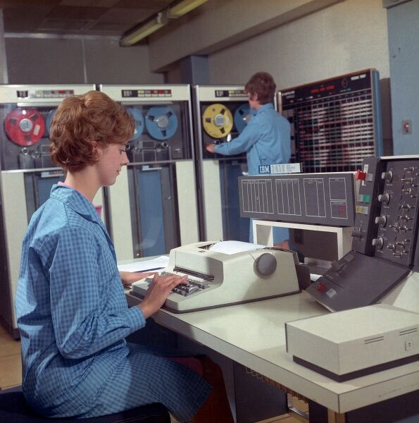 A female computer technician sits at an IBM 1410, in a promotional photograph for this business computer system. Photograph by Heinz Zinram