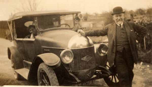 A jolly chap leaning happily on the bonnet of his new car, a soft-top Bellanger Freres 3.2 Litre Tourer (French), as his female passenger (his wife?) leans out of the vehicle to get in the shot