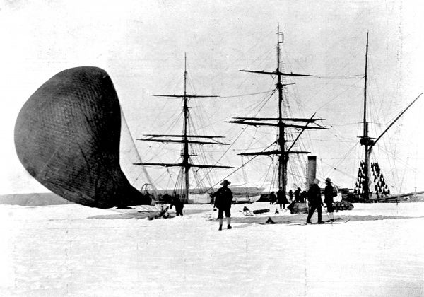 Photograph showing members of the National Antarctic Expedition of 1901-4 deflating an hydrogen balloon, with the Polar Research Ship 'Discovery' in the background, Antarctic, 4th February 1902. This was the end of the very first balloon flight
