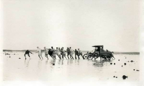 British officers and men pulling a car out of the mud, somewhere in the Middle East
