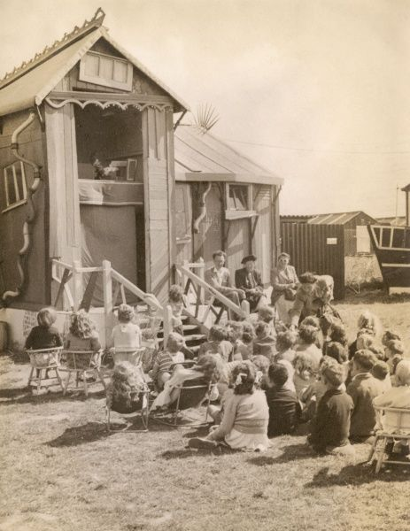 A group of children sit obediently together enthralled by the gratuitous violence of a Punch and Judy Show in an unidentified location, though the corrugated huts and clothing indicates this is some time shortly after World War II. Date: c.1946