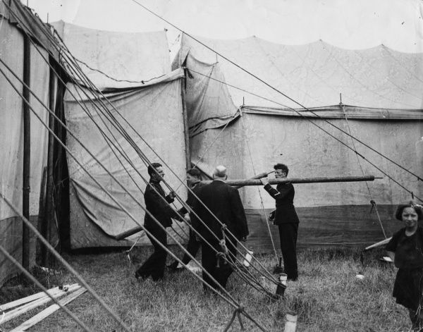 Workmen erecting a fairground marquee. Date: early 1930s