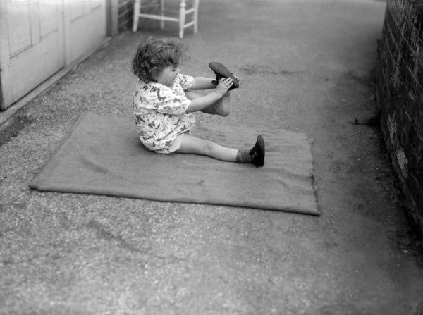 A National Adoption Society little girl, sitting on a blanket as she learns how to put on her own shoes. Date: early 1930s
