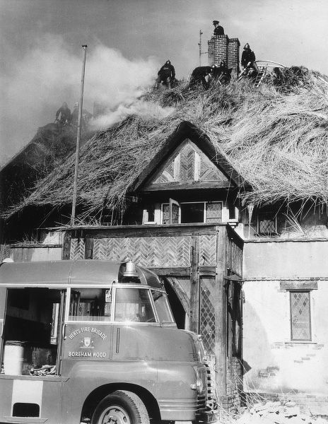 The Fire Brigade deals successfully with a fire that has broken out on a thatched roof Date: 1950s