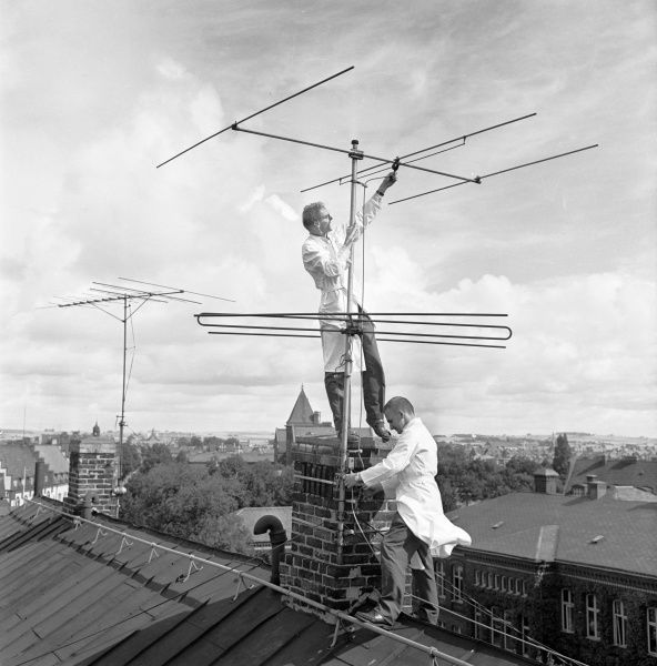 In the beginning of Television, in Sweden. The aerial is mounted by two men in white coats Date: 1950s