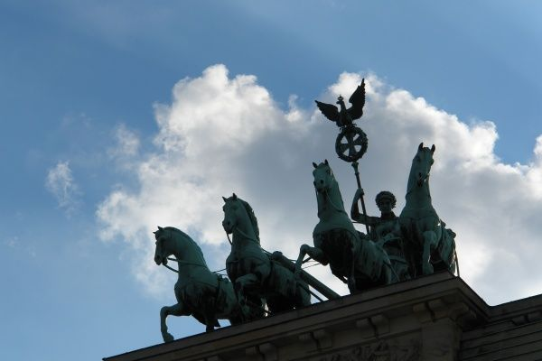 The Quadriga (four horses drawing a chariot), seen here in silhouette against the sky, on top of the Brandenburg Gate in Berlin, Germany