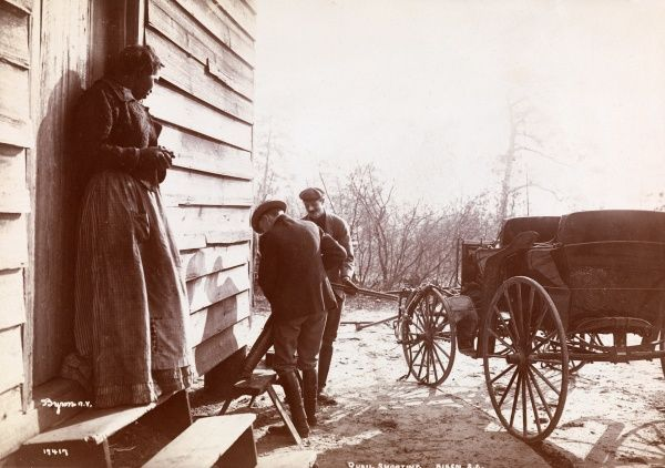 Quail Shooting, Aiken S.C. Two men at hunting shack with shotgun, black woman onlooking; carriage visible