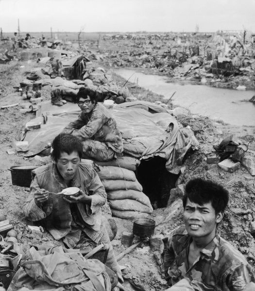 Quang Tri: Three Vietnamese soldiers rest, (one eating rice), among the rubble of their town which has been destroyed by Viet Cong attacks
