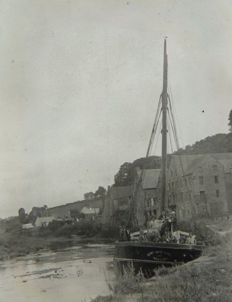 View of the quayside at Haverfordwest, Pembrokeshire, Dyfed, South Wales, with a boat in the foreground and buildings in the background. There are people on the boat, which is called Mary Jane (?) of Milford
