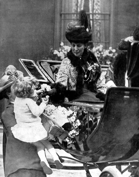 Photograph showing Queen Alexandra, receiving a rose from a small child, during one of the Queen's annual drives through London on Alexandra Rose Day, 1925