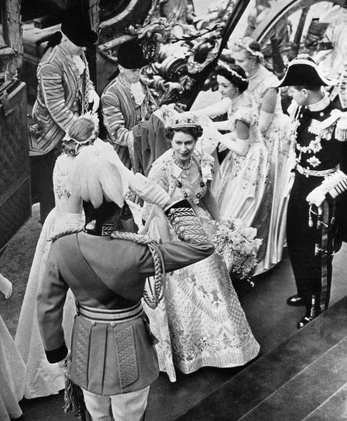Queen Elizabeth II, accompanied by her Maids of Honour alights from the golden State Coach on arriving at Westminster Abbey for her Coronation in June 1953. Prince Philip, Duke of Edinburgh awaits her. The bouquet she carried included orchids