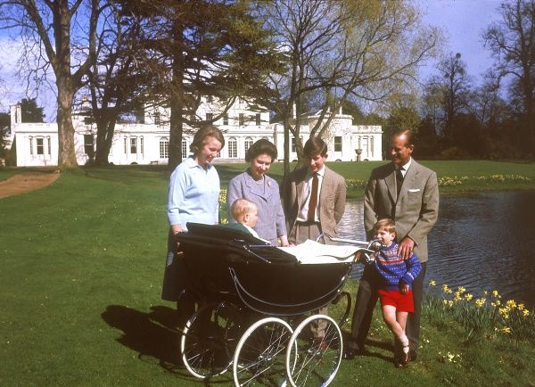 The royal family photographed at Frogmore in April 1965. The Queen, Prince Philip, Duke of Edinburgh, Princess Anne, Prince Charles, Prince of Wales, Prince Andrew, Duke of York all stand around a pram admiring the one year Prince Edward, Earl of Wessex
