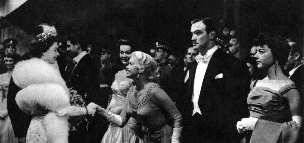Actress Jayne Mansfield curtseys to Queen Elizabeth II, following the Royal Film Performance at Leicester Square, London. Between the Queen and Jayne Mansfield are Michael Craig and Anne Heywood. On the right, awaiting presentation, are Stanley Baker