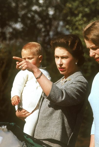 Queen Elizabeth II, holding a one year old Prince Edward (Earl of Wessex) points something out to his elder sister, Princess Anne at Frogmore in April 1965. Date: 1965