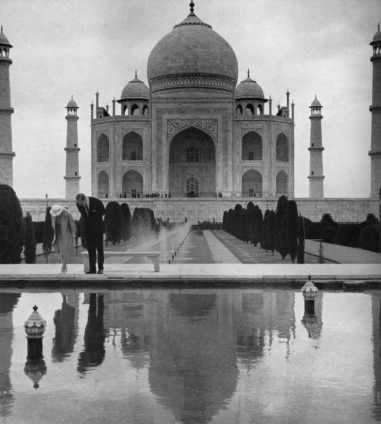 Queen Elizabeth II and Prince Philip, Duke of Edinburgh gaze in the ornamental lake which reflects the formal beauty of the Taj Mahal behind them during the royal tour of India and Pakistan in 1961. Date: 1961