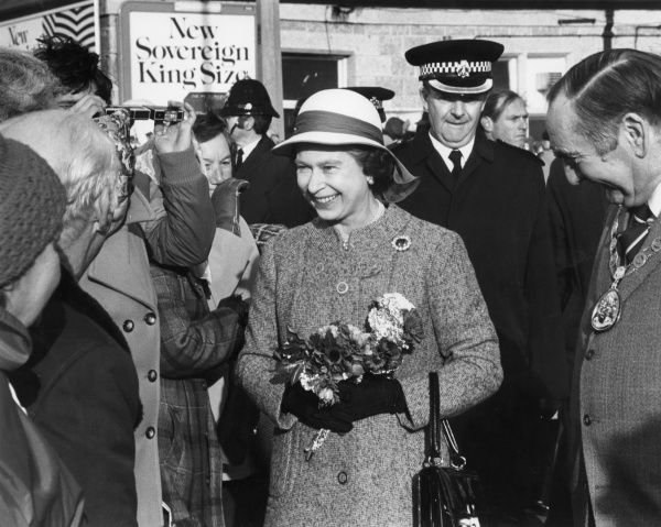 A smiling Queen Elizabeth II visiting Cornwall. She is accompanied by the local Mayor and a Police Officer and has been presented with a small bouquet of flowers