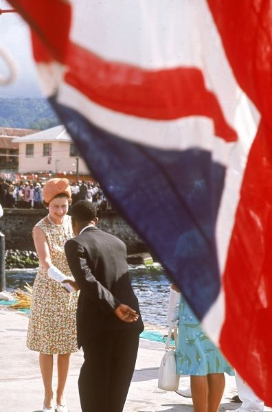 In the shadow of a Union Jack flag, Queen Elizabeth II is greeted on her arrival at St Kitts during a five week tour of the West Indies in 1966. Date: 1966