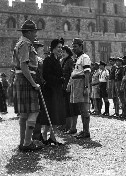 Queen Elizabeth II chatting with international scouts in the Windsor Castle quadrangle, where she took the salute at a scouts march past. Accompanying her is the chief scout Lord Rowallan. Date: 27th April 1952