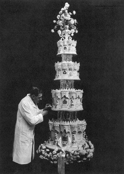 The final preparations being carried out to Queen Elizabeth's wedding cake. A wedge is prepared for her to cut with her bridegroom's sword