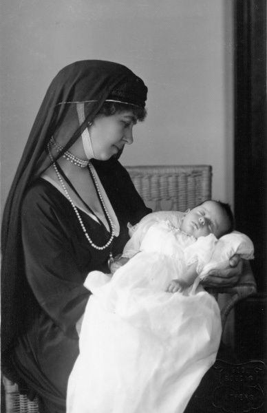 Queen Sophie of Greece holding her granddaughter Alexandra in 1921. The Queen wears mourning here for her son Alexander, the baby's father, who died five months before the child was born, following a bite from a monkey. The curious head dress