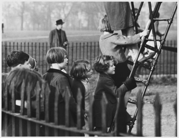 A group of young children queue to climb the ladder in the playground