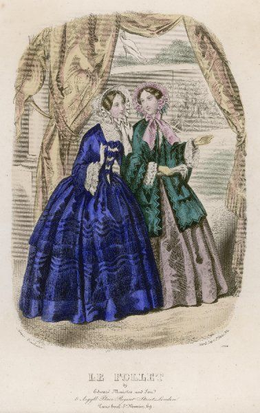 Dark blue dress: skirt trimmed with fringing & waves of ribbon, open body with bows arranged like echelles. Green mantle with black reversed vandyke trim
